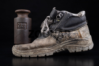 Dirty work shoe and 2 kg weight. Used crush resistant shoes for production workers.