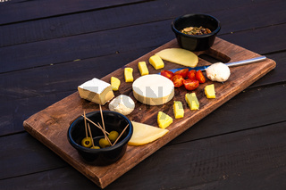 Cheese plate. Assortment of various cheese with nuts and olives.