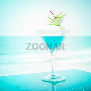 Blue margarita cocktail at tropical ocean beach