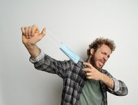 Played or got rid of young man holding protective medical mask in front of face ready to end quarantine, with curly hair, wearing plaid shirt and olive t-shirt under. White background