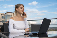 Woman working on laptop at office while talking on phone. Portrait of young smiling business woman calling her best friend, having break, telling something funny, sitting in cafe.