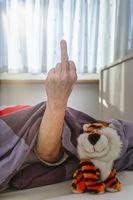 Seniorin im Bett zeigt Stinkefinger
