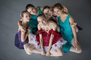 Five young ballerinas sitting on the floor