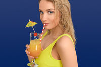 Young blond woman sipping an exotic fruit cocktail