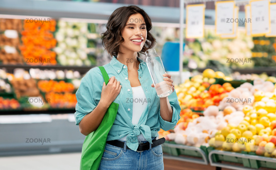 woman with bag for food shopping and glass bottle