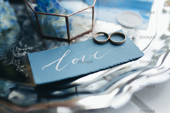 Wedding rings at wedding invitation with decorations