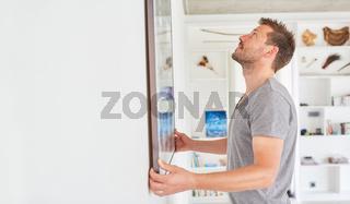 Mann befestigt Bilderrahmen an einer Wand