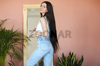 Stylish young woman near mirror and plants