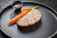 Minimalistic gourmet meatloaf slice with sliced carrot and ketchup as closeup on a modern design plate with copy space