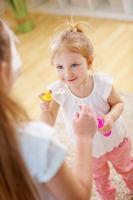 Mädchen hilft kleiner Schwester beim Seifenblasen