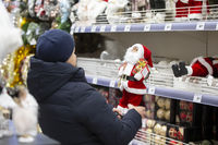 December 10, 2020. Belarus, the city of Gomil. Christmas Fair. An elderly woman chooses a santa claus toy in the store. Grandmother buys a present for her grandson for Christmas.