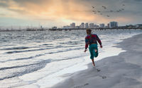 Unrecognizable man running on beach during sunset