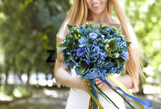 Happy woman with bouquet of green and blue flowers