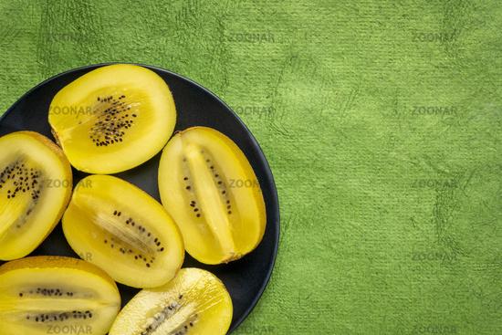 cut gold kiwifruit berries on black plate