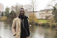 Fashionable Black Man Wearing Beige Coat Smiling in Public Park