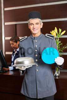 Concierce beim Check-In hält Schild