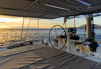 Idyllic scenery glowing sun down Ocean calm water view from catamaran flybridge open deck, modern luxury yacht equipped with navigation dashboard devices, wealthy lifestyle freedom concept. Spain