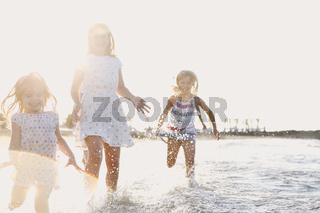 Happy kids running in sea water