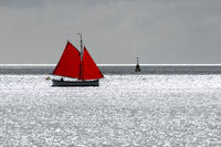 Sailing boat with red sail against the glare of the sun