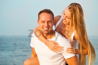 Laughing couple enjoying nature over sea background. Attractive man and woman at the beach