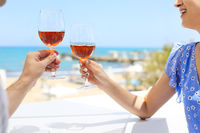 Hands of couple enjoying glasses of rose wine on tropical beach