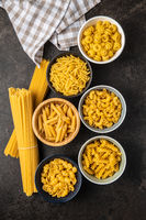 Various types of raw italian pasta in bowls.