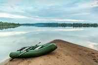 Rubber boat on a gentle sandy shore near the river.