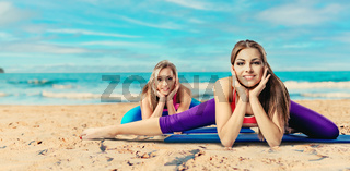 Two beautiful young women doing stretching exercise on the beach