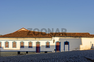 Facade of old house in colonial style architecture with blue windows and door