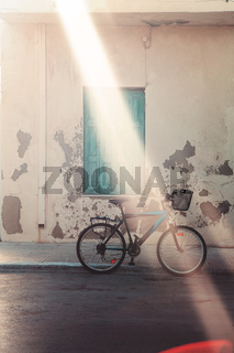 Bicycle parked near wall on street