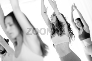 Group of young sporty attractive women in yoga studio, practicing yoga lesson with instructor, standing, stretching and relaxing after workout . Healthy active lifestyle, working out. Black and white