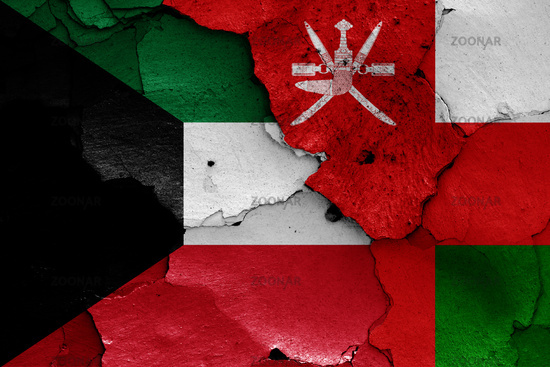 flags of Kuwait and Oman painted on cracked wall