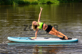 Young blonde woman planking sideward on SUP in water
