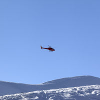 Helicopter in blue clear sky and snowy ski slope