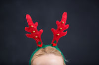 Happy smiling young woman wearing Christmas deer horns. Christmas party. Beauty, fashion.