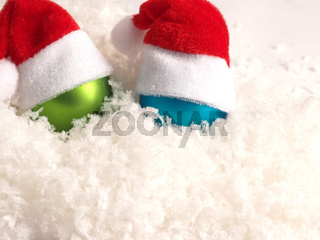 Old Christmas baubles with hat of Santa on snow