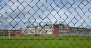 High School Building Behind A Fence