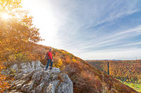 Senior male hiker standing on a cliff ledge and looking at a beautiful hilly autumn landscape in the Swabian Jura