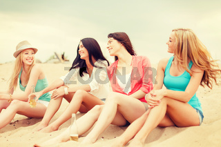 smiling girls with drinks on the beach