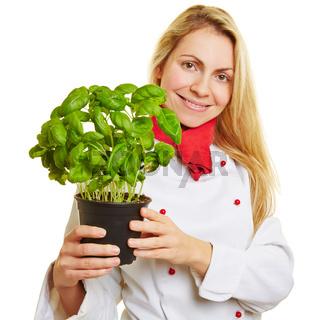 Frau als Köchin mit einem Topf Basilikum