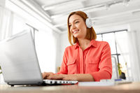 woman in headphones with laptop working at home