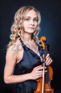 Beautiful violinist on a dark background