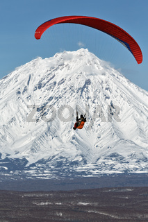 Paraglider flying on background of active volcano
