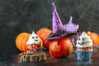 Halloween ghost cupcakes and pumpkin with a witch hat.