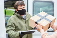 Paketbote mit Mundschutz übergibt Paket