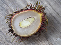 Half of a rambutan on a wooden background.