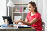 student girl with tablet pc learning at home