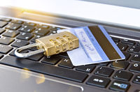 Credit card with padlock on computer keyboard symbolising secure online banking or payment