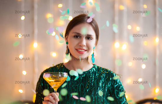 Woman in party outfit holding glass with champagne