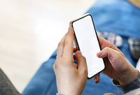 Caucasian woman hands holding a smart phone in a modern living room. White screen for copy space.